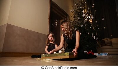Mom and daughter sitting under the Christmas tree open gifts. The girl untying the ribbon of the gift. Overall plan