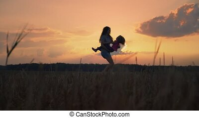Mom and daughter spinning around hugging at sunset with flying hair