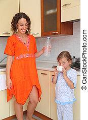 Mom and daughter standing in kitchen. Mom keeps empty bottle of milk. little girl drinking milk from cup