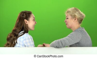 Mom and daughter talking on talking on various topics. Green screen. Side view