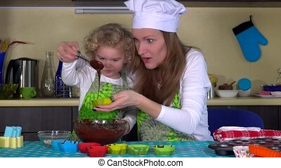Mom and daughter three years pour batter into cup cake forms...