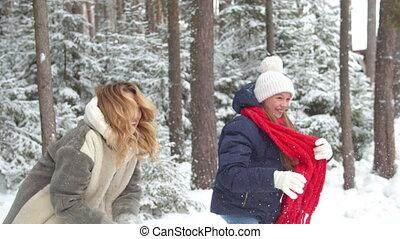 Mom and daughter outdoors play snowballs. Medium shot
