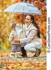 Mom and daughter under the umbrella hide from the rain.