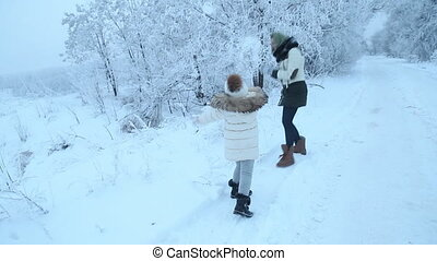 Mom and daughter walking through the woods - Mom and...