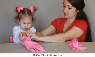 Mom and daughter wear rubber gloves and start to clean. The...