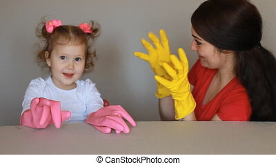 Mom and daughter wear rubber gloves and start to cleaning...