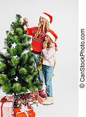 Mom and daughter, wearing Santa Claus hats, decorate the Christmas tree together,