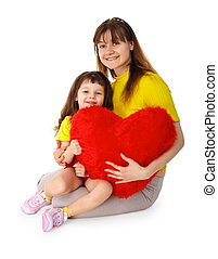Mom and daughter with a toy heart in hands