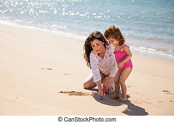 Portrait of a young mother and her little girl drawing something together on the sand