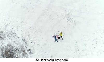 Mom and daughters laying on snow - Mom and two daughters...