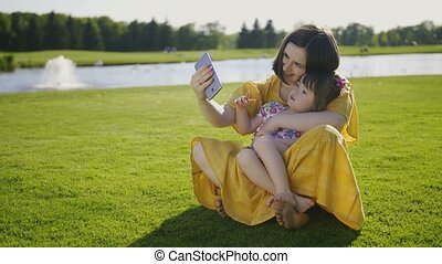 Mom and down syndrome girl making selfies in park