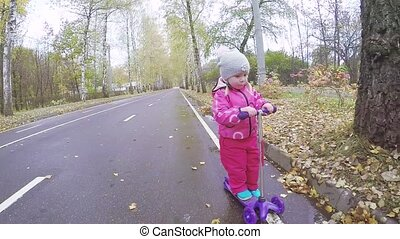 Mom and girl on scooter - Young girl teaches a baby girl to...