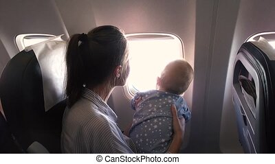 Mom and her baby in airplane look out the window