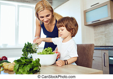 Mom and her child are preparing food in the kitchen.
