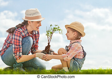 girl plant sapling tree - Mom and her child girl plant ...