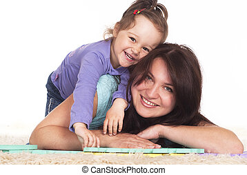 mom and her child rest - family of a two playing on carpet