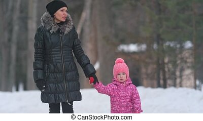 Mom and her cute little daughter walking in the winter park