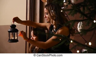 Mom and her daughter are lighting a lantern with a live fire under the Christmas tree and the girl blowing out a burning candle.
