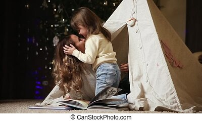 Mom and her daughter are sitting in a tent inside their house. The daughter hugs her mother who read her a skirt. Love in the family
