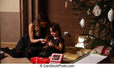 Mom and her daughter sit under a decorated Christmas tree at...