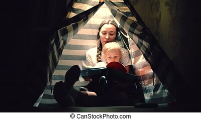 Mom and her little baby read a book together in a teepee in...
