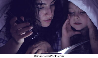 Mom and her little daughter are reading fairy tales for the night, they are wrapped in a warm blanket and immersed in the story of the plot. 4K.