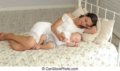 Mom and her newborn baby are sleeping in the bed in the bedroom. Portrait.