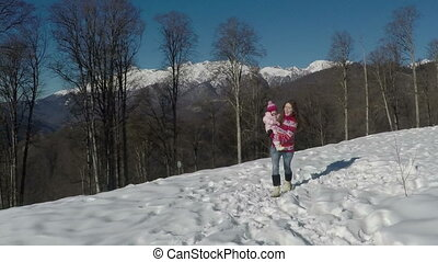 Mom and her pretty daughter in the winter. slow motion