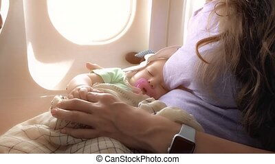 Mom and her sleeping baby traveling by plane - Mum and her...