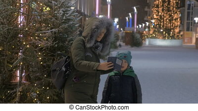 Mom and kid making winter selfie in the street with Christmas illumination