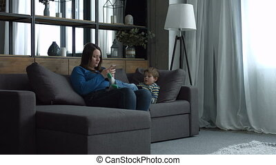 Mom and kid relaxing on couch with digital devices
