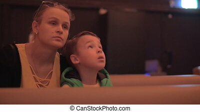 Mom and kid spending leisure at the cinema