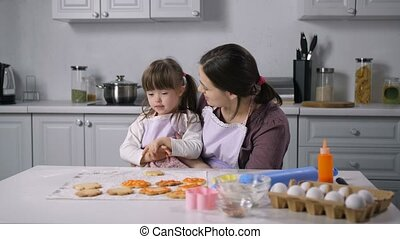 Loving caring beautiful mother and cute little daughter with special needs communicating and learning body language while spending leisure in the kitchen while baking delicious cookeis.