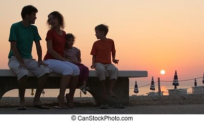 Mom and kids and father are sitting on bench