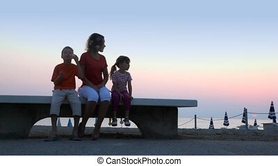 Mom and kids are sitting on beach bench