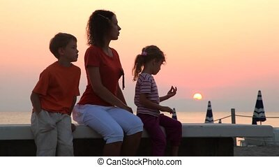 Mom and kids are sitting on bench and sun rises