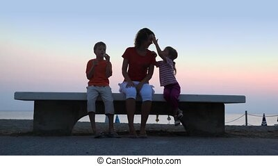 Mom and kids are sitting on bench and boy make bubbles