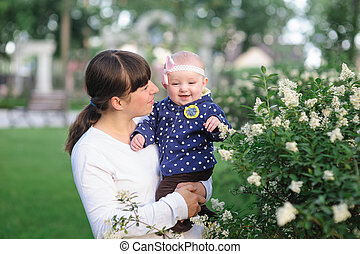 mom and little baby daughter walking in the spring park