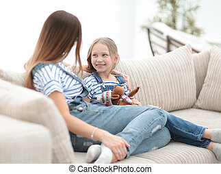 mom and little daughter sitting on the couch in a cozy living room