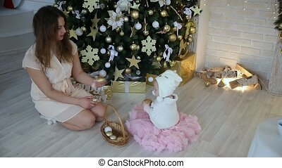 Mom and little girl and christmas toys, balls and gurland