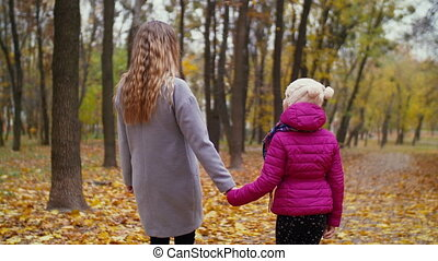 Mom and little girl spending leisure in autumn park