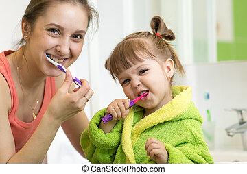 Mom and little kid daughter brushing teeth in bathroom