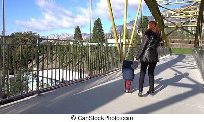 mom and little son go over the bridge