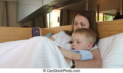 Mom and little son lie on the bed in the morning and play games on the phone.