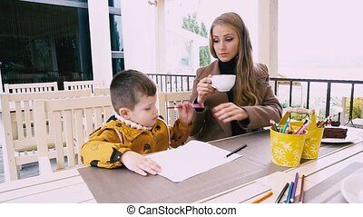 mom and little son paint in a restaurant