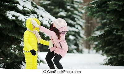 Happy family playing snowballs in the winter snowy day