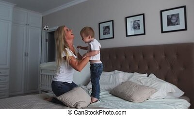 Mom and son are playing on the bed in a bright bedroom, a...