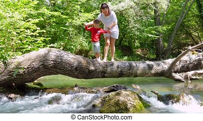 Mom and Son are walking on a log that fell across the river to sit on it.