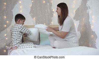 Mom and son beat each other with pillows having a good mood