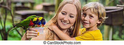 Mom and son feed the parrot in the park. Spending time with kids concept. BANNER, LONG FORMAT